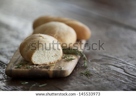 Fresh Garlic bread and herbs on a cutting board - stock photo