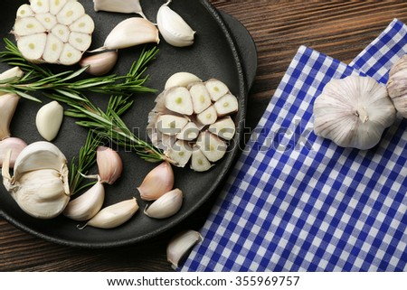 Fresh garlic with rosemary in black pan near blue checkered cotton napkin on wooden background, close up - stock photo