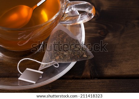 Fresh glass cup of tea with saucer and teabag close up. Set on a dark wooden table with space for text - stock photo