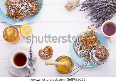 Fresh golden home new trend funnel cake waffles with honey, tea, a slice of lemon on a white wooden background with lavender flowers. The concept is simple homemade cakes. selective Focus - stock photo