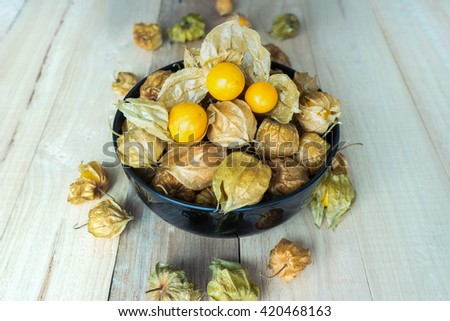 Fresh Gooseberry Cape is delicious fruit in a black bowl on wooden background - stock photo