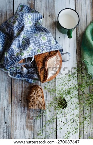 Fresh grain bread with cup of milk over rustic white table. Rustic style. Top view. - stock photo
