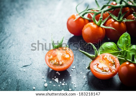 Fresh grape tomatoes with basil and coarse salt for use as cooking ingredients with a halved tomato in the foreground with copyspace - stock photo