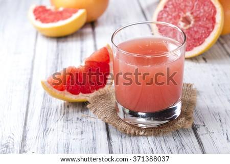 Fresh Grapefruit Juice on rustic wooden background (close-up shot) - stock photo
