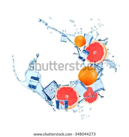Fresh grapefruits falling in water splash, isolated on white background - stock photo