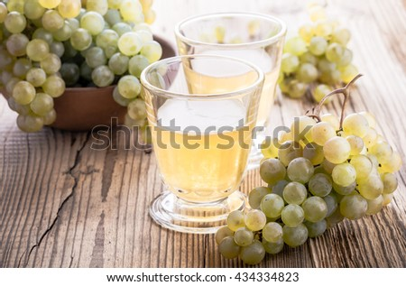 Fresh grapes and freshly squeezed grape juice on rustic wooden table, harvest time - stock photo