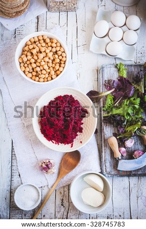 Fresh grated ingredients ready to prepare veggies burger with beet, chickpeas, egg, spinach leaves, wholegrain floor, cheese on a white rustic wooden table. See series for recipe. - stock photo