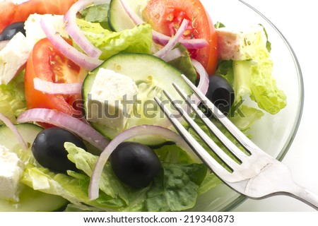 Fresh greek salad with feta cheese cubes and black olives - stock photo