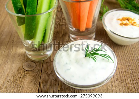 fresh Greek Tzatziki yogurt dip (sauce) and assorted vegetables on wooden table - stock photo