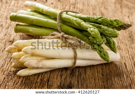 Fresh green and white asparagus on a wooden background - stock photo
