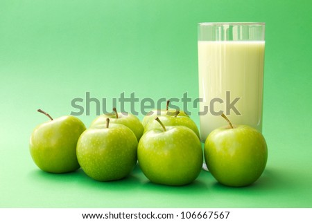 Fresh green apple yogurt drink surrounded by green apples - stock photo
