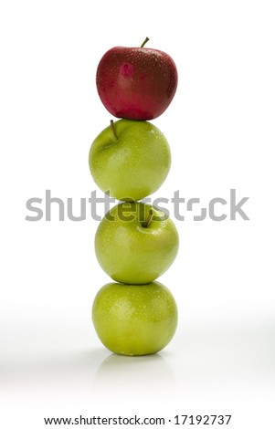 Fresh green apples stacked on top of one another with a red apple on top - stock photo