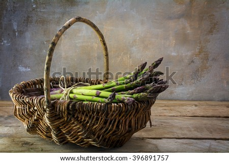 fresh green asparagus in a basket on a rustic wooden table in front of a vintage wall with copy space in the background, selected focus - stock photo