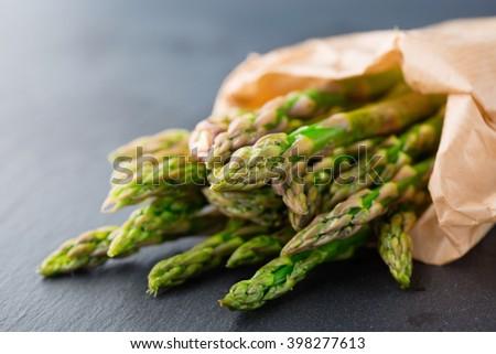 Fresh green asparagus on black background, selective focus - stock photo