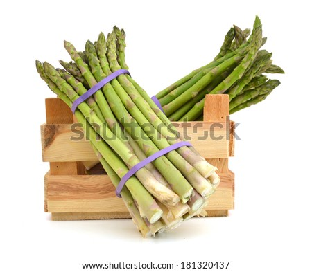 fresh green asparagus shoots in a wooden crate on a white background  - stock photo