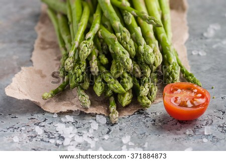Fresh green asparagus with tomatoes and sea salt on a marble table - stock photo