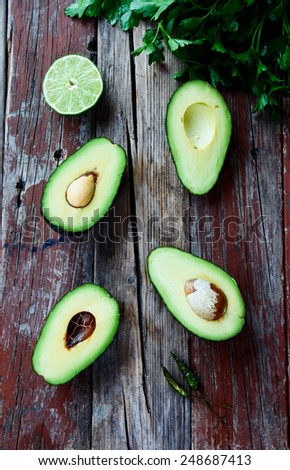 Fresh, green avocado, lime and parsley on rustic wooden background - healthy food, diet or cooking concept. Top view. - stock photo
