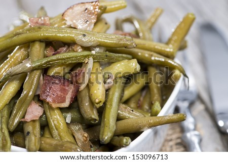 Fresh Green Beans with Ham and Onion on vintage wooden background - stock photo
