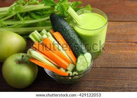 Fresh green celery and cucumber with the chopped carrots in a glass bowl near the juice in a glass and green apples on a brown wooden background - stock photo