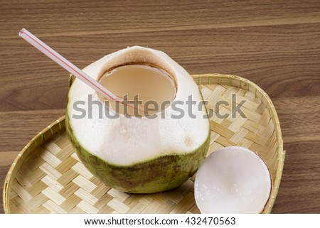 Fresh green coconut isolated on wooden background. DOF and copy space - stock photo