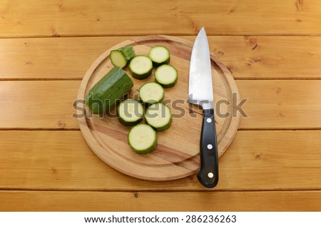 Fresh green courgette being sliced with a sharp kitchen knife on a wooden chopping board - stock photo
