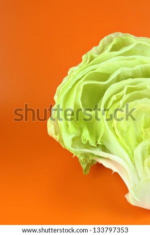 Fresh Green Iceberg lettuce on orange background . - stock photo