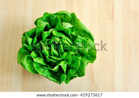 fresh green lettuce from above on wooden table - stock photo
