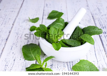 Fresh green mint in mortar on color wooden background - stock photo