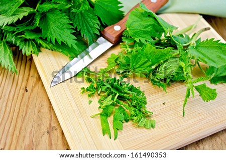 Fresh green nettle incised on a wooden board with a knife and napkin - stock photo
