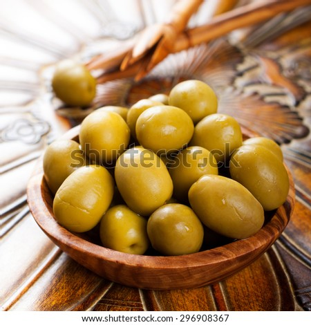 Fresh green olives in olive wood bowl on rustic wooden background.  Selective focus. - stock photo