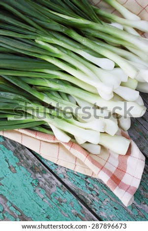 Fresh green onions on a wooden table - stock photo