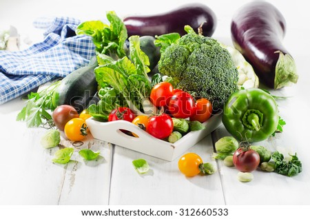 Fresh green organic vegetables on white wooden background. Selective focus - stock photo