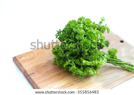 Fresh green parsley on wooden cutting board - stock photo