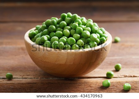 fresh green pea in bowl on wooden background - stock photo