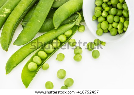 Fresh green pea pods and peas in bowl, on white background  - stock photo