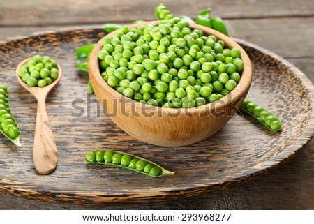 Fresh green peas in bowl on wooden tray, closeup - stock photo