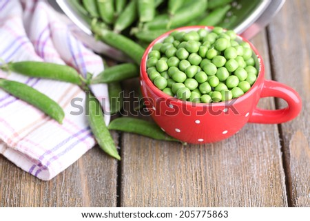 Fresh green peas in colander and red cup on wooden background - stock photo