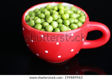 Fresh green peas in red cup isolated on black background - stock photo