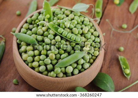 Fresh green peas in wooden bowl on wooden background - stock photo