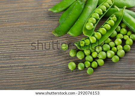 Fresh green peas on wooden table, closeup - stock photo