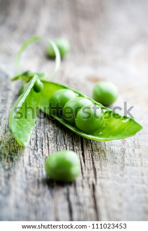 Fresh green peas on wooden table, selective focus - stock photo