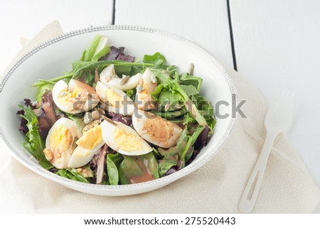 fresh green salad with boiled eggs , seeds and drizzled with balsamic vinaigrette dressing - stock photo