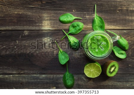 Fresh green smoothie with kiwi, lime and spinach on rustic wooden background. Top view. Selective focus. - stock photo