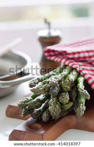 Fresh green spring asparagus on a wooden cut board on a kitchen table ready to cook or to eat. Closeup, vertical - stock photo
