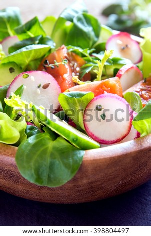 Fresh green spring vegetable salad with cucumber, radish, tomatoes and seeds in wooden bowl close up, selective focus - stock photo