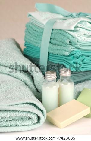 Fresh green towels, washcloths, soap and shampoo - stock photo