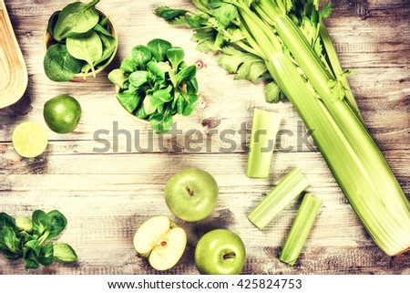 Fresh green vegetables and fruits on wooden background. Detox and diet concept - stock photo
