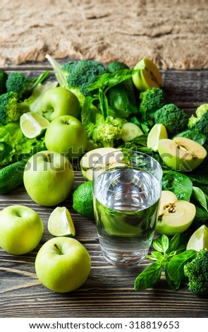 Fresh green vegetables and glass of still water on vintage wooden background. Detox, diet or healthy food concept - stock photo