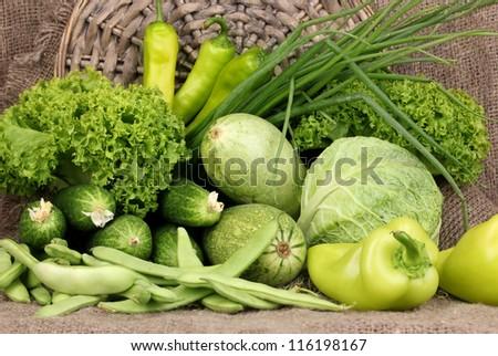 fresh green vegetables on sackcloth background - stock photo