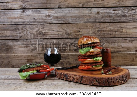 fresh grilled beef huge hamburger served on wood plate with red wine glass chili pepper rosemary green salad leaf and forged vintage antique cutlery over wooden table empty space for text - stock photo